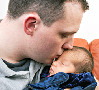 a newborn baby is held by her dad as he kisses her cheek rK0IP9RSi