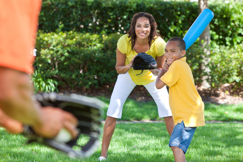 An African American family playing baseball on the yard