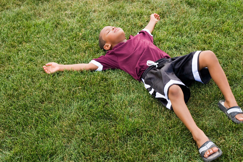 Child in soccer uniform lying on grass