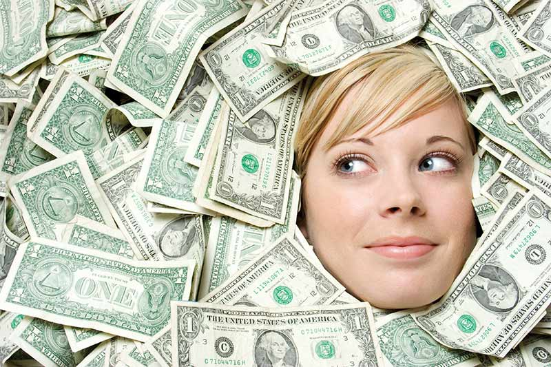 Woman under a pile of money