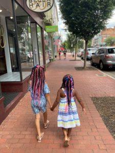 Two little girls holding hands walking on Caroline St. in Downtown Fredericksburg