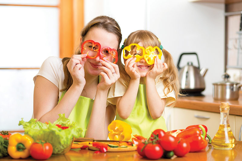 Mom and daughter cutting vegetables.